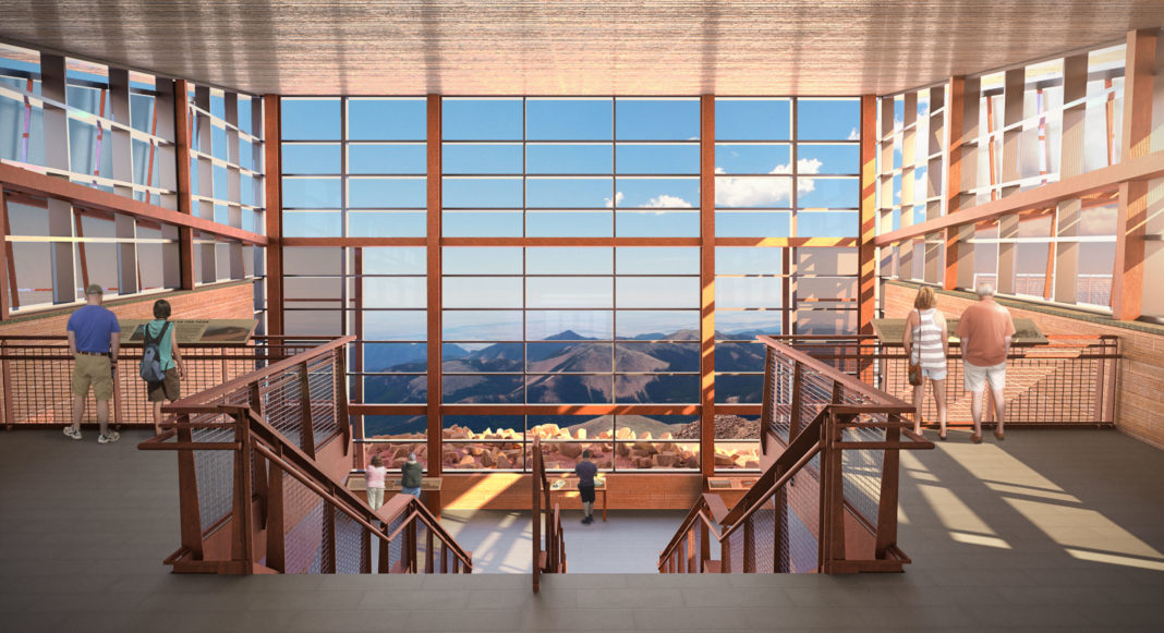 walking down a grand staircase and looking through a multistory glass curtain wall at a striking mountain range with blue sky and puffy white clouds beyond them