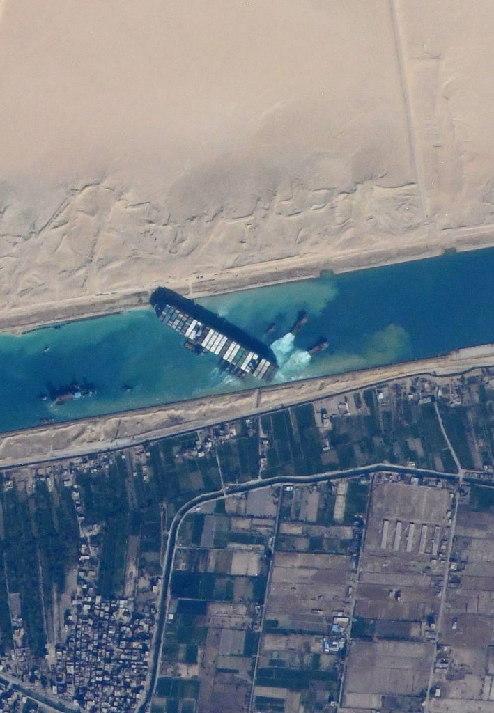 aerial view of a large container ship stuck on either shore of a narrow canal
