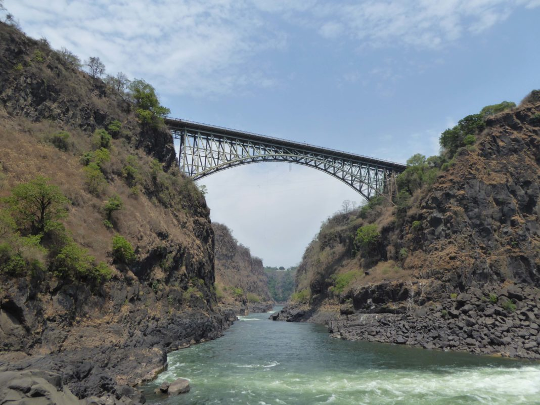 victoria falls bridge spans between two cliffs above a river 420 ft below