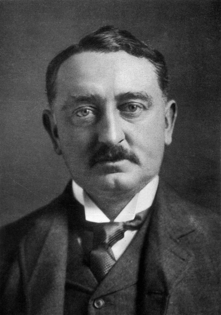 black and white photo of middle aged white man with a mustache wearing a suit and tie