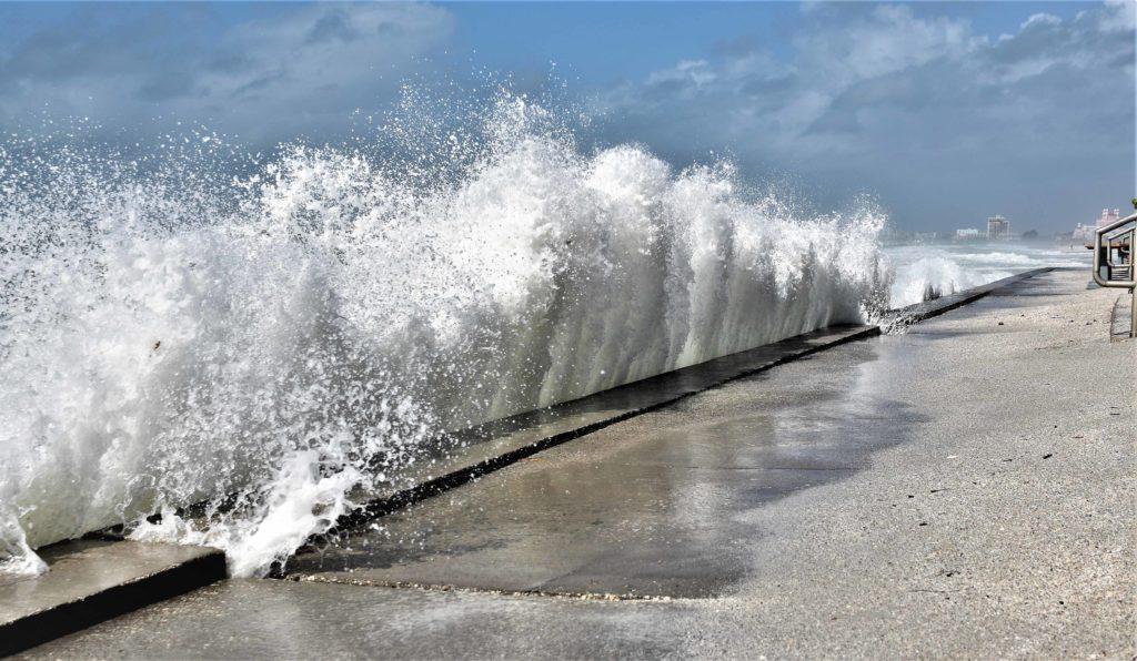 waves crashing at a flood wall at a beach
