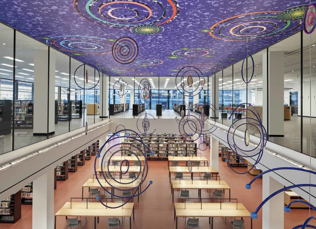interior photo of the two story great reading room with its desks and books and its multicolor ceiling with various designs