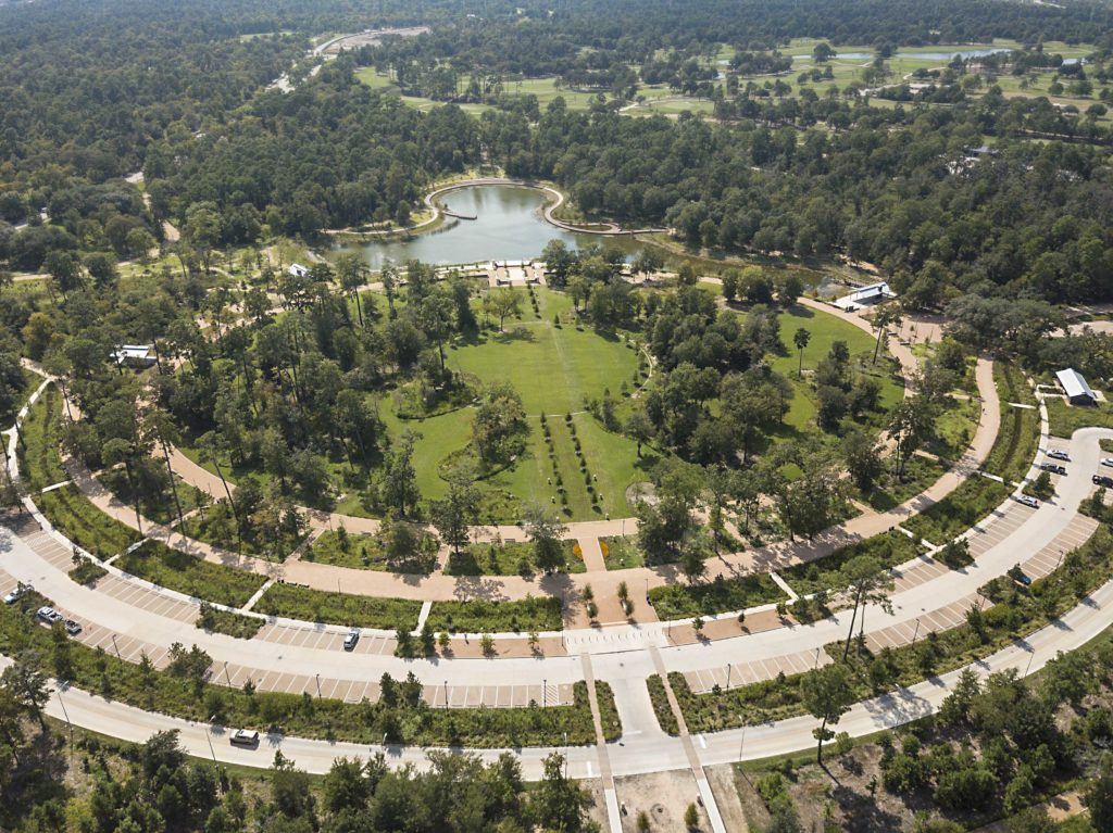 aerial shot of a park with a lake shaped kind of like an octopus and walkways, trees, and parking spaces
