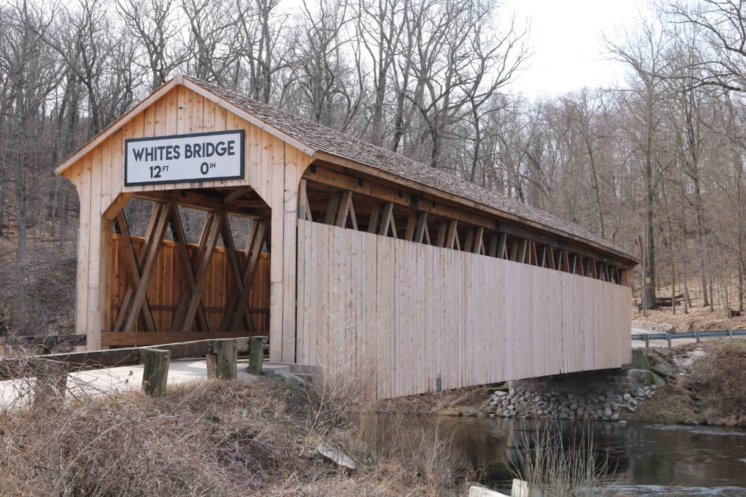ebuilt two-lane wooden bridge whose sides are covered in wood planks