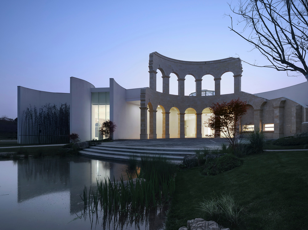 a modern fragment of a roman series of arches stands by a pavilion on one side and a water body on the other at dusk
