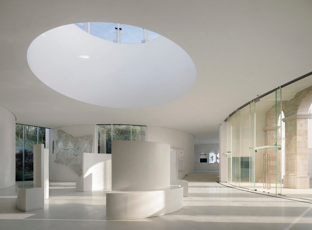 a stark white central hall with rounded, circular elements and details is encased in a series of perimeter glass walls