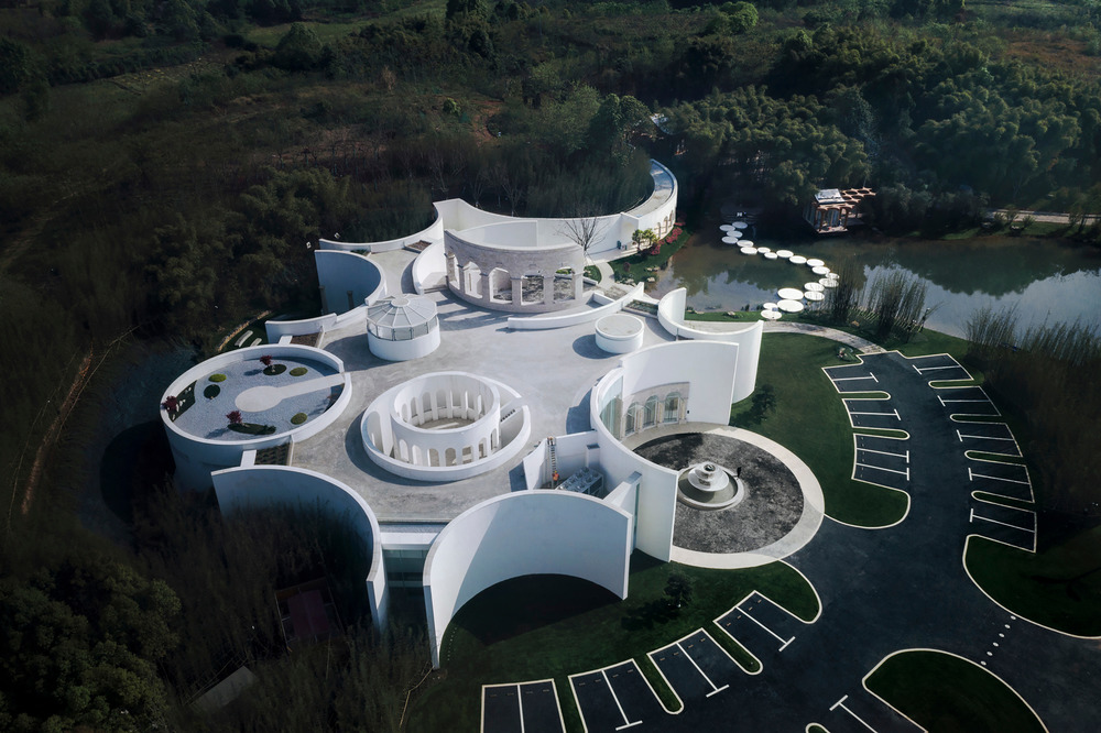 aerial view of a white pavilion with curving walls and a white stone path through the water to the trees beyond