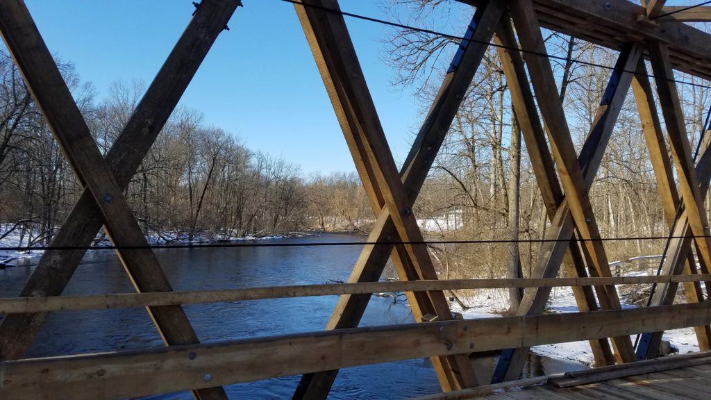 view out to the lake through the criss crossed planks on the bridge