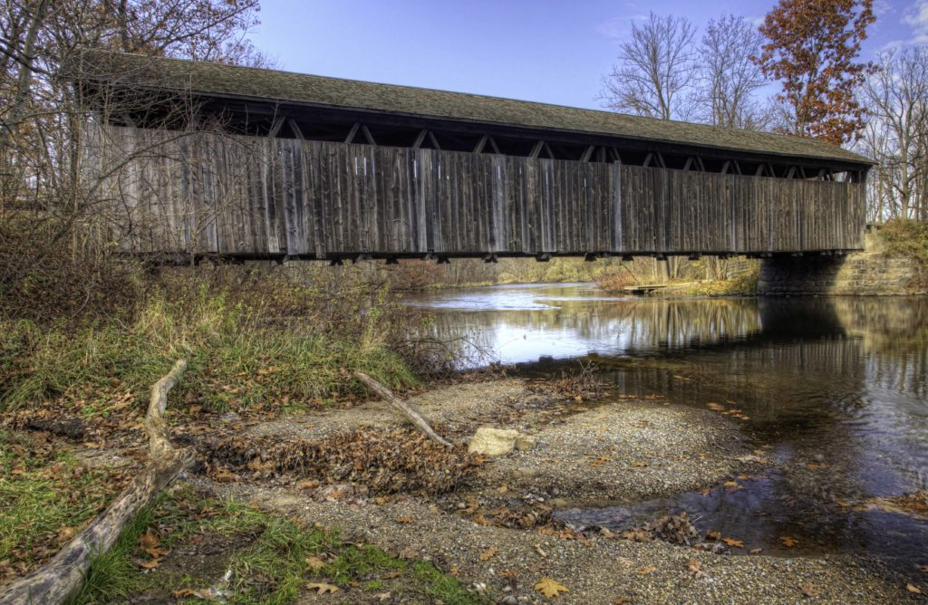 one lane wooden bridge built in 1869 spanning a small body of water. it has a gabled roof and wood siding