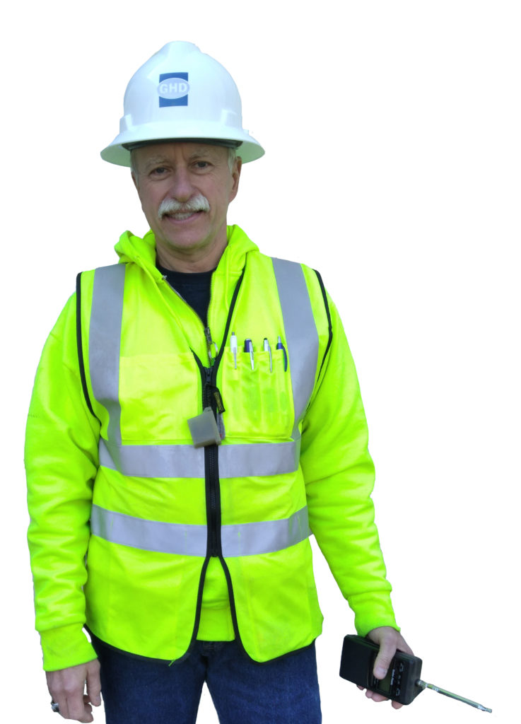 older white male with white mustache smiling at the camera. he is wearing a hard hat safety jacket and jeans and he's carrying a walkie talkie