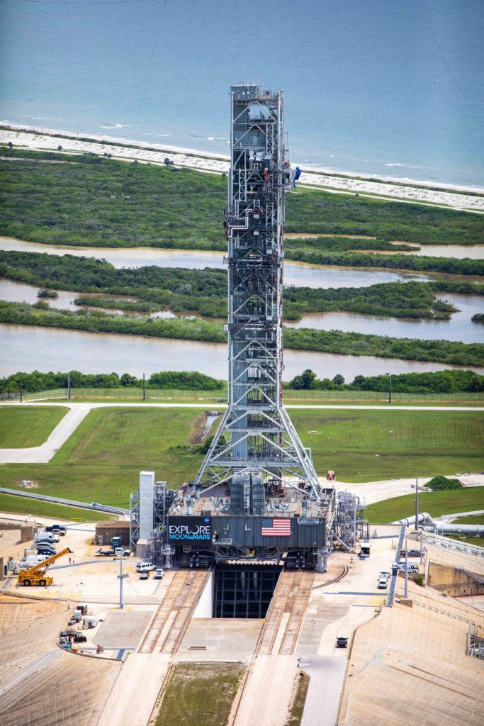 An aerial view of Launch Complex 39B with Exploration Ground Systems' mobile launcher for the Artemis 1 mission on the pad with wetlands, a beach, and the ocean visible just behind