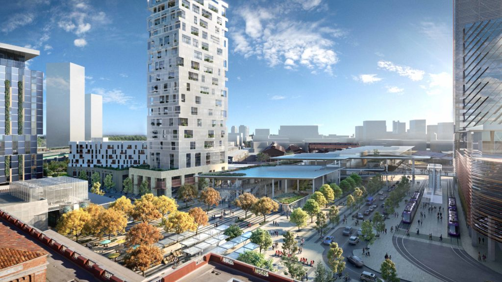 overlooking a plaza with plenty of greenery and trees and a large white tower with glass windows