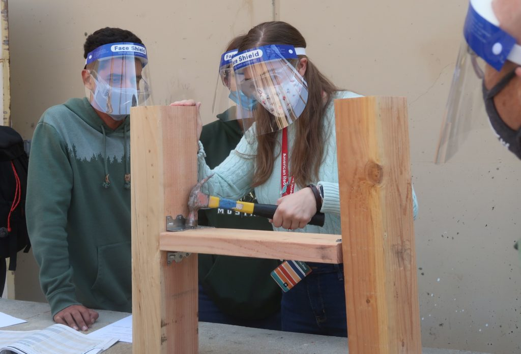 female student testing a timber connection embedded in wood. two male students and the instructor are observing.