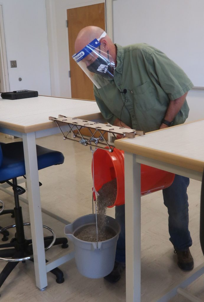 male instructor demonstrates testing the strength of trusses by pouring gravel from one bucket into another