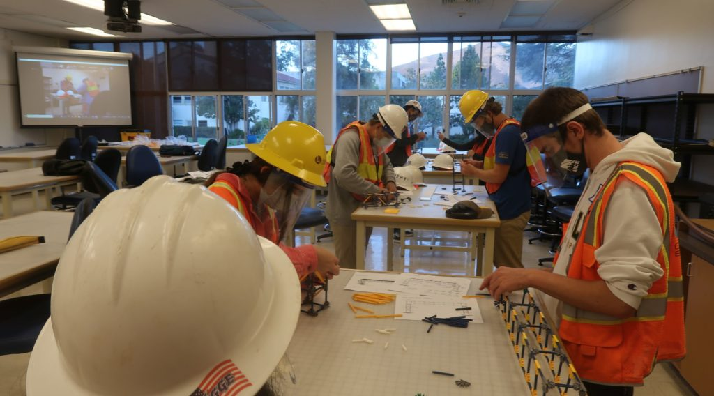 students in safety vests, face shields, and hard hats take part in a design, bid, build exercise where they assemble structures