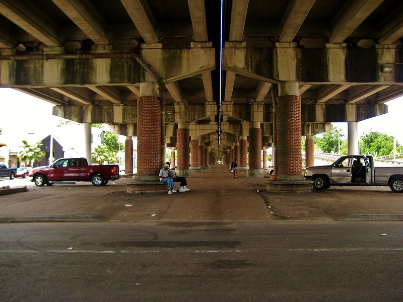 two men sit under an enormous overpass, the Claiborne Expressway in New Orleans