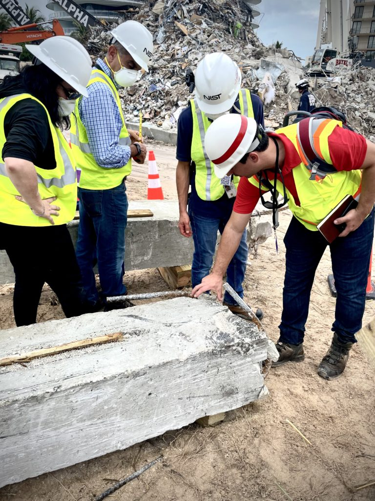 a building element from the Champlain Towers South partial collapse is examined by four people in yellow vests, hard hats, and masks