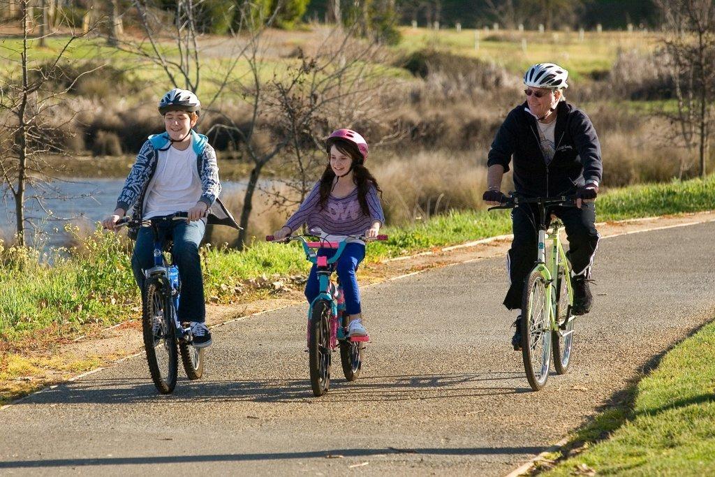 three people ride down a bike path